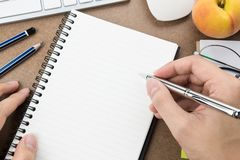 Man is going to write something on blank notebook page.  royalty free stock photos