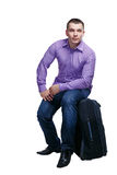 Man going on trip. Man going on a trip and sits on a suitcase, isolated on white background Royalty Free Stock Image