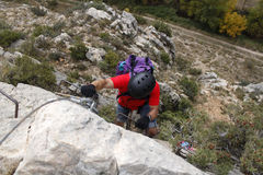 Man going up doing a via ferrata. In Spain Stock Images