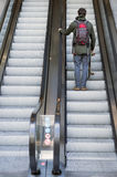 Man going up on escalator Stock Photos