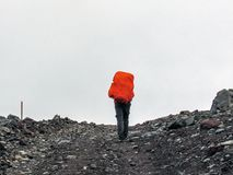 Man going up hill with huge heavy backpack stock photos