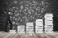 A man is going up using a stairs which are made of white books. Educational icons are drawn on the black chalkboard. Royalty Free Stock Photo