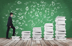 A man is going up using a stairs which are made of white books. Educational icons are drawn on the green chalkboard. Stock Photos