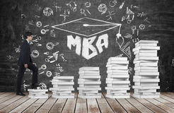 A man is going up using a stairs which are made of white books to reach graduation hat Royalty Free Stock Image