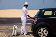 Man going for vacation. Man opening a tank of car, standing with a luggage on a side of the road Stock Images