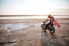 Man in golden in american cape sitting on his motocycle Royalty Free Stock Photos
