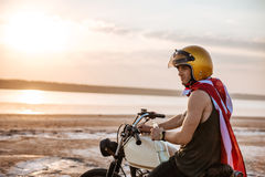Man in golden in american cape sitting on his motocycle Stock Images