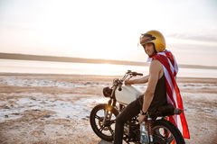 Man in golden in american cape sitting on his motocycle Stock Photography