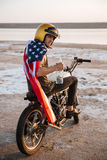 Man in golden in american cape sitting on his motocycle Royalty Free Stock Images