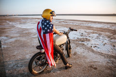 Man in golden in american cape sitting on his motocycle Royalty Free Stock Image