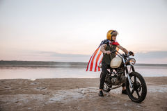 Man in golden helmet and american flag cape driving motorcycle Stock Images