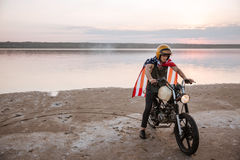 Man in golden helmet and american flag cape driving motorcycle Royalty Free Stock Image