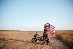 Man in golden helmet holding american flag at the desert Stock Photo