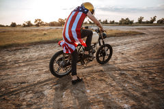 Man in golden helmet starts his motorcycle Royalty Free Stock Image