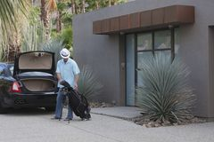 Man With Golf Bag Outside House Stock Photography