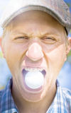 Man with golf ball in mouth Stock Image