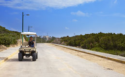 Man by golf car on the seashore. Mexico. Women Island Royalty Free Stock Photography