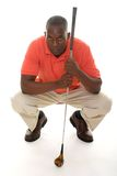 Man WIth Golf Club. Casual young African American man in a bright orange golf shirt with a golf club lining up a putt Stock Photography
