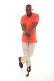 Man WIth Golf Club. Casual young African American man in a bright orange golf shirt holding a golf club Royalty Free Stock Images