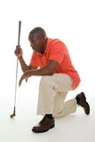 Man WIth Golf Club. Casual young African American man in a bright orange golf shirt with a golf club lining up a putt Royalty Free Stock Images