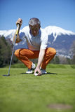 Man golfer putting his golf ball on the green. Aligning it to a hole, with snowcapped mountains on the background Stock Photography