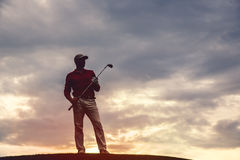 Man golfer silhouette. Silhouette of man golfer with golf club at sunset Stock Photo