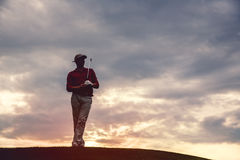 Man golfer silhouette. Silhouette of man golfer with golf club at sunset Stock Photos