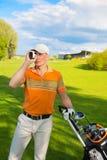 Man golfer watching into rangefinder Royalty Free Stock Image