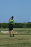 Man Golfing. Man on beautiful golf course in Cozumel Mexico on the fairway swinging a club wearing a green shirt and shorts Royalty Free Stock Photos