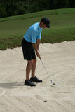 Man Golfing From Sand Bunker. Man on golf course with a ball and club in a sand trap or bunker Stock Photos