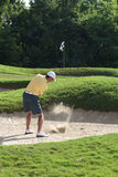 Man Golfing from Sand Bunker. Man in yellow shirt golfing from a sand trap and swinging the club and hitting the ball Stock Photography