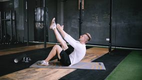 Intermediate no equipmetn exersize to endurance, sit ups. Man in good fit does abs exercises or curl up for improving sports training, single-leg toe touches stock video