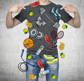 A man in a good physical form is pointing out the fingers on the colourful sport icons. Concrete background. a concept of a health Stock Image