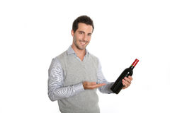 Man with a good wine bottle in hands. Happy winegrower showing wine bottle to camera royalty free stock photography
