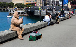 A man with a gorilla costume begging for tips. Wellington, New Zealand - February 10, 2017: A man wearing a gorilla costume, is begging for tips at the Royalty Free Stock Photography