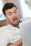 Man got scared in front of tablet Stock Photo