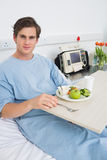Man in gown having mean in hospital Stock Image