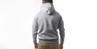 Man grå hoodie för grabbblanko, tröja, åtlöje som isoleras upp Plommoner royaltyfri bild