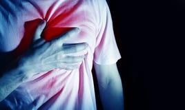 Man grabb i en skjorta för vit t på en svart bakgrund i blåa händer för en färghåll på hans hjärta, hjärtaatack, sträng hjärtesor royaltyfria foton