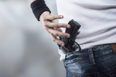 Man grabbing his pistol. Man grabbing quickly a pistol, hands close up Stock Photo