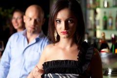 Man grabbing woman. Man grabbing arm of woman at a bar.  Focus on woman Stock Image