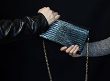 Man grabs a handbag from the hands of a woman, a black background, theft of bags stock photos