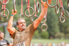 Man Grabs Onto Suspended Rings At Extreme Obstacle Course Race. Conyers, GA, USA - August 22, 2015:  A man grimaces as he swings from rings suspended from wood Royalty Free Stock Photo