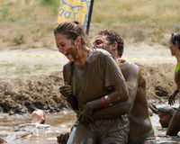 Man grabs a woman in the mud pit Royalty Free Stock Photography