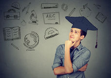Man with graduation hat looking up thinking Royalty Free Stock Photos