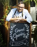 Man with grand opening blackboard stock photography