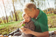 Man with granddaughter exploring plant stock photo