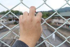 Man grasp the bar of cage with the defocus of city background. Man grasp the bar of cage with the defocused of city background Royalty Free Stock Photos