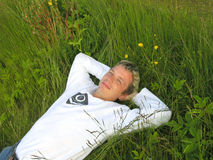 Man in the grass 2. 25 year old man lying in the grass on his back, smiling, relaxing. Room to crop Royalty Free Stock Photos