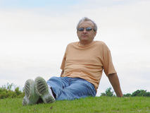 A man on the grass. A man sitting on the grass Royalty Free Stock Images